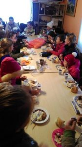 Children sitting around 2 long tables eating a hot meal