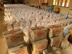100's of bags of rice packed in clear plastic bags with boxes of oil