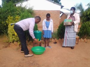 Malawi leader giving a young child a bucket and showing her how to wash her hands with mother holding box of soaps