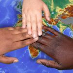 Three hands making contact over a world map